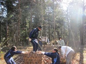 落ち葉を詰める生徒